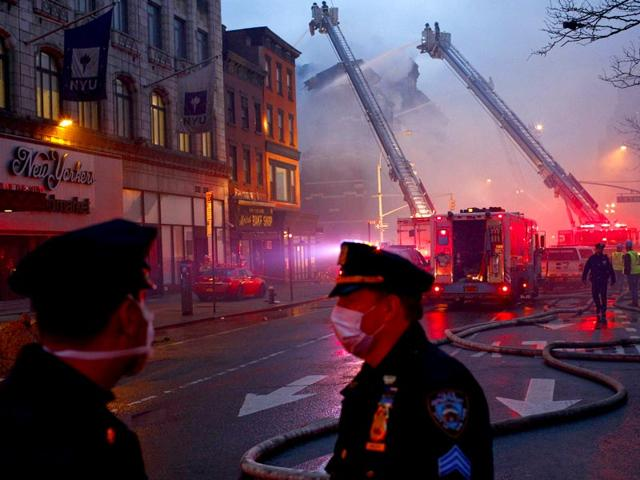Police-officers-stand-guard-while-firefighters-battle-a-blaze-at-a-commercial-and-residential-block-in-New-York-s-East-Village