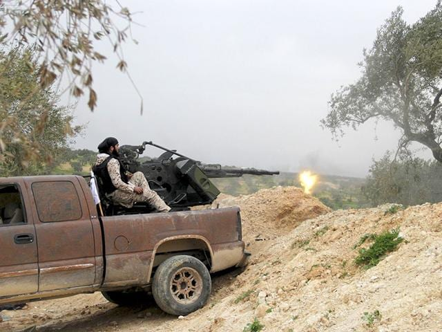 Rebel-fighters-from-Suqour-al-Sham-Brigade-fire-their-weapons-towards-forces-loyal-to-Syria-s-president-Bashar-al-Assad-that-are-fleeing-Idlib-city-after-rebel-fighters-took-control-of-the-area-Reuters