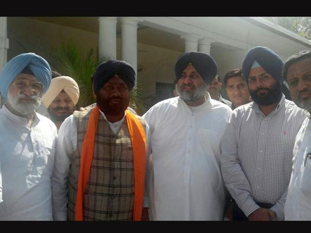 Gurbakshish-Singh-Bhatti-in-orange-robe-with-Sukhbir-Singh-Badal-and-other-party-members-HT-Photo