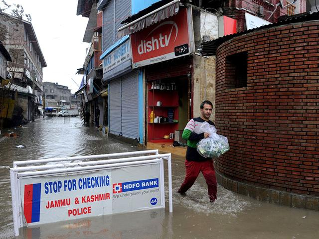 A-shopkeeper-carries-goods-down-a-flooded-road-in-Srinagar-after-heavy-rainfall-on-March-29-2015-Parts-of-Srinagar-were-waterlogged-following-sustained-rains-since-March-28-AFP-PHOTO