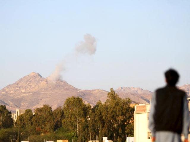 A-man-looks-on-as-smoke-billows-from-military-barracks-in-the-Jabal-al-Jumaima-mountain-following-an-air-strike-near-Sanaa-Reuters