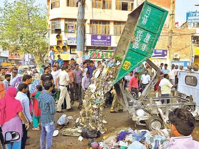 East-Delhi-Municipal-Corporation-workers-dump-garbage-on-the-road-in-Shahdara-in-protest-against-non-paywent-of-salaries-on-time-Sonu-Mehta-HT-Photo