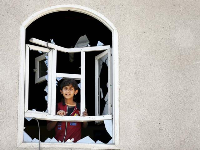 A-boy-looks-through-his-damaged-home-near-Sanaa-Airport-Yemen