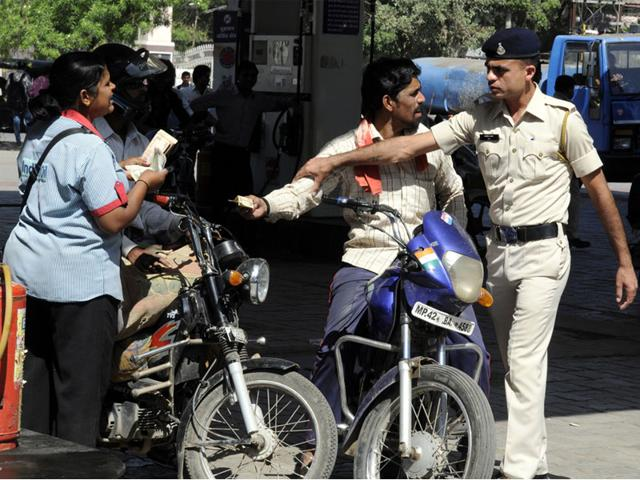 For-the-people-of-Indore-Wednesday-was-chaotic-at-various-petrol-pumps-around-the-town-While-the-police-were-determined-to-make-people-follow-the-no-helmet-no-petrol-directive-many-were-seen-carrying-helmets-just-as-a-token-to-buy-petrol-Shankar-Mourya-HT-photo