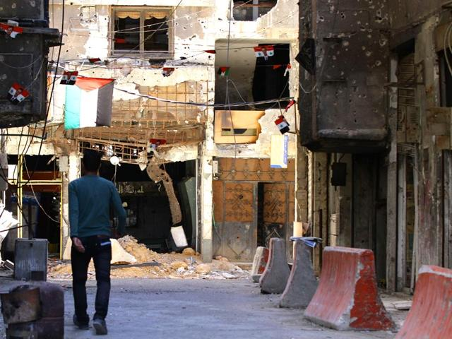 A-file-picture-shows-a-man-walking-past-bullet-riddled-buildings-at-the-Yarmuk-Palestinian-refugee-camp-in-Damascus-AFP-Photo