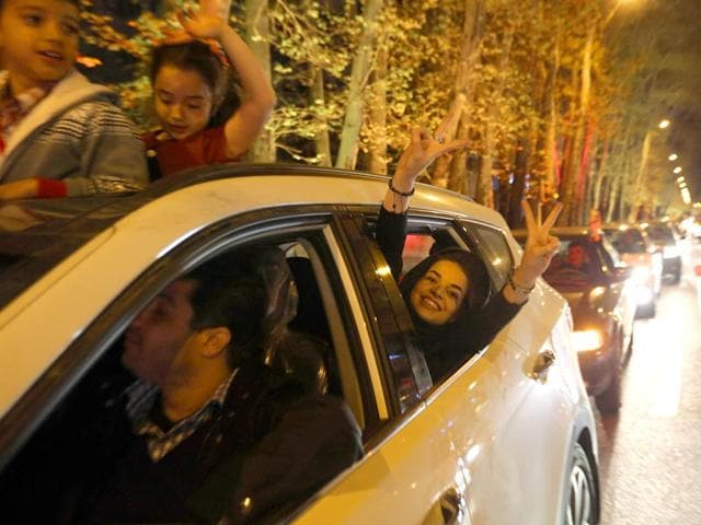 A-woman-flashes-the-V-for-Victory-sign-out-of-a-car-window-as-people-celebrate-on-Valiasr-street-in-northern-Tehran-after-the-announcement-of-an-agreement-on-Iran-nuclear-talks-AFP-Photo