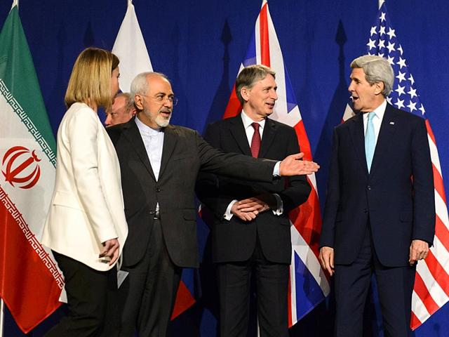 In-this-file-photo-from-left-EU-high-representative-for-foreign-affairs-and-security-policy-Federica-Mogherini-Iranian-foreign-minister-Mohammad-Javad-Zarif-British-foreign-secretary-Philip-Hammond-and-US-secretary-of-state-John-Kerry-line-up-for-a-press-announcement-after-a-new-round-of-nuclear-Iran-talks-in-the-Learning-Center-at-the-Swiss-Federal-Institute-of-Technology-EPFL-in-Lausanne-Switzerland-AP-Photo
