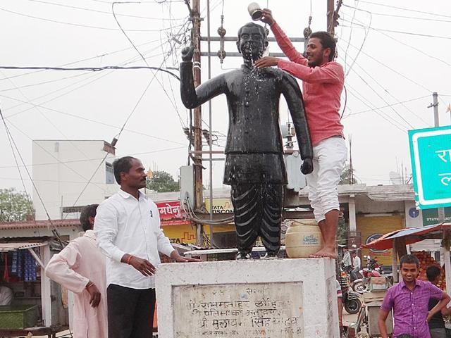 Activists-of-the-Lohia-Vichar-Manch-wash-a-statue-of-socialist-leader-Ram-Manohar-Lohia-with-gangajal-soon-after-former-Bihar-CM-Jitan-Ram-Manjhi-garlanded-it-HT-Photo