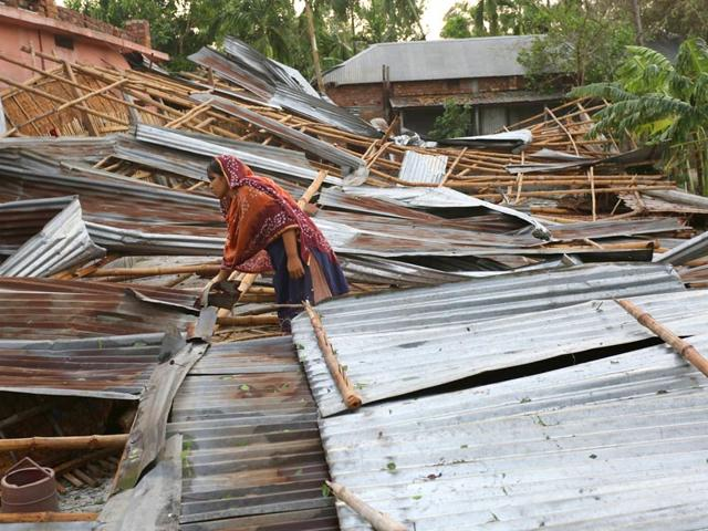 In-this-photograph-taken-on-April-5-2015-a-Bangladeshi-victim-gathers-her-belongings-near-her-home-which-was-destroyed-during-storms-in-Bogra-some-200km-from-Dhaka-AFP-Photo