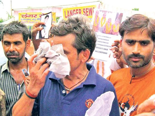 People-hold-pictures-of-their-relatives-who-went-missing-after-the-June-2013-disaster-in-Dehradun-HT-file-photo