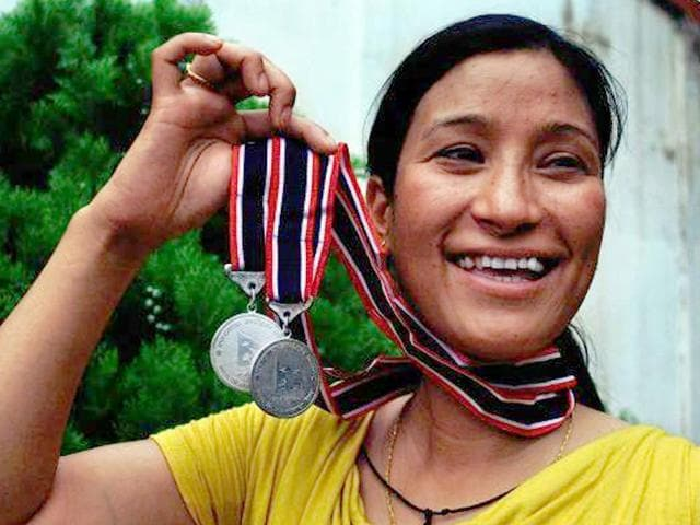 Anshu-Jamsenpa-had-achieved-her-earlier-world-record-in-2011-when-she-climbed-the-Everest-twice-in-a-span-of-10-days-In-this-picture-the-mountaineer-from-Arunachal-Pradesh-shows-off-medals-she-received-from-the-Nepal-Government-for-her-feat-AFP-Photo