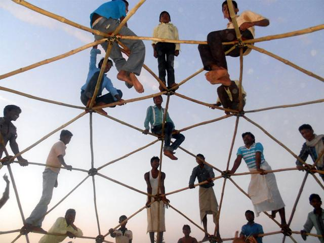Tribals-test-the-strength-of-a-bamboo-dome-roof-in-Dharampuri-village-of-Jhabua-district-HT-photo
