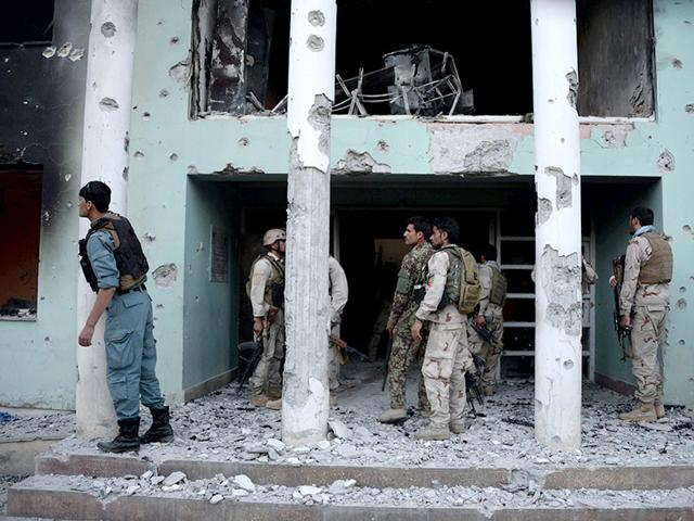 Afghan-security-personnel-examine-damage-to-a-building-at-a-court-complex-following-a-suicide-attack-in-Mazar-i-sharif-on-April-9-2015-At-least-10-people-died-April-9-2015-when-Taliban-insurgents-wearing-military-uniforms-mounted-a-six-hour-gun-and-grenade-siege-on-a-court-complex-in-northern-Afghanistan-an-assault-highlighting-the-country-s-fragile-security-situation-AFP-Photo