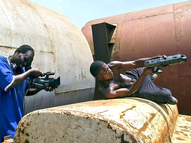 Ramon-Film-Productions-and-founder-of-Wakaliwoods-Isaac-Nabwana-directs-and-films-a-scene-in-one-of-their-up-coming-movies-in-Kampala-on-March-4-2015--It-is-being-filmed-in-a-scrap-yard-in-Wakaliga-a-slum-in-Uganda-s-capital-Kampala-now-baptised-Wakaliwood-It-is-going-to-be-as-big-as-Nollywood-Bollywood-or-even-Hollywood-there-s-no-reason-why-not-writer-director-editor-and-producer-Isaac-Nabwana-boasted-of-Uganda-s-informal-film-industry-boldly-insisting-studios-in-Nigeria-India-and-the-United-States-will-get-a-run-for-their-money-AFP