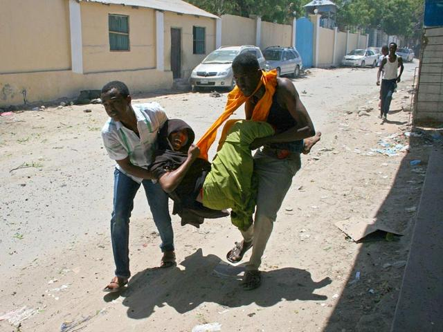 People-carry-a-wounded-person-at-the-scene-of-a-car-bomb-outside-the-Education-Ministry-in-Mogadishu-AFP-Photo