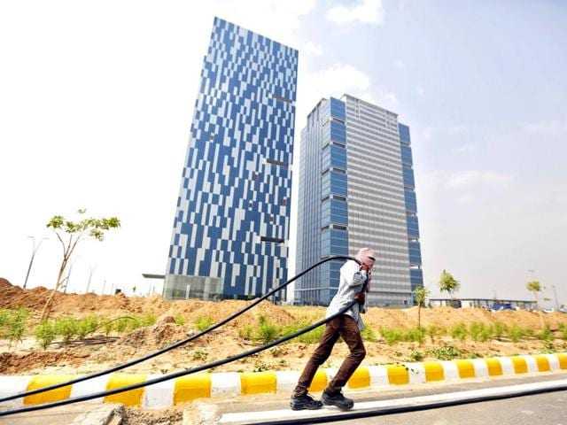 A-labourer-pulls-a-cable-in-front-of-two-office-buildings-in-Gujarat-International-Finance-Tec-City-GIFT-at-Gandhinagar-in-Gujarat-Reuters-Photo