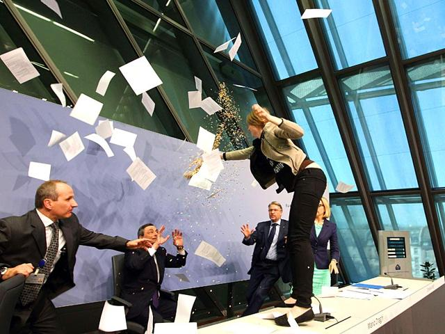 A-woman-throws-papers-and-confetti-as-she-interrupts-a-press-conference-by-Mario-Draghi-C-president-of-the-European-Central-Bank-ECB-following-a-meeting-of-the-Governing-Council-in-Frankfurt-Main-Germany-AFP-Photo
