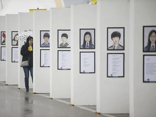 A-mourner-looks-at-pictures-of-victims-from-the-sunken-ferry-Sewol-at-the-official-memorial-altar-for-the-victims-in-Ansan-on-the-occasion-of-the-first-anniversary-of-the-ferry-disaster-that-killed-more-than-300-passengers-April-16-2015-REUTERS