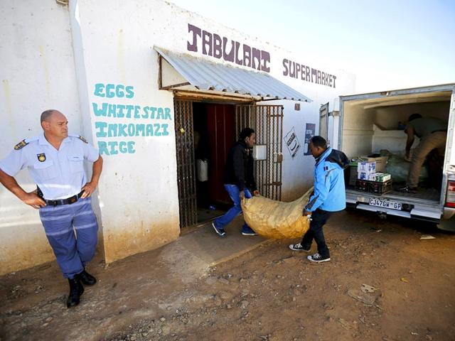 A-police-officer-L-looks-on-as-a-foreign-nationals-clear-items-from-their-shop-for-fear-of-attacks-in-Primrose-outside-Johannesburg-Reuters