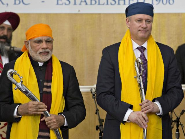 Narendra-Modi-and-Canada-s-prime-minister-Stephen-Harper-hold-swords-presented-to-them-during-a-visit-to-the-Gurdwara-Khalsa-Diwan-in-Vancouver-AFP-Photo