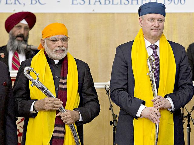 Canada-s-Prime-Minister-Stephen-Harper-right-and-Indian-Prime-Minister-Narendra-Modi-hold-swords-presented-to-them-during-a-visit-to-the-Gurdwara-Khalsa-Diwan-in-Vancouver-British-Columbia-on-April-16-Reuters-Photo