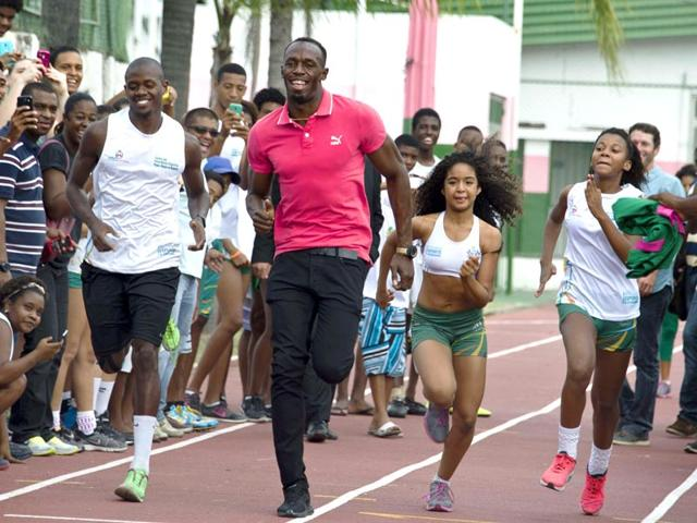Jamaican-sprinter-and-six-time-Olympic-gold-medallist-Usain-Bolt-runs-with-children-during-a-visit-to-a-sports-complex-at-the-Mangueira-shantytown-in-Rio-de-Janeiro-on-April-16-2015-AFP-Photo