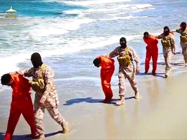 This-image-made-from-the-video-by-militants-in-Libya-claiming-loyalty-to-the-Islamic-State-group-purportedly-shows-Egyptian-Coptic-Christians-in-orange-jumpsuits-being-led-along-a-beach-each-accompanied-by-a-masked-militant-AP-photo