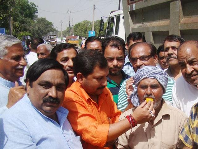 Haryana-chief-minister-s-OSD-Amarendra-Singh-orange-shirt-offering-sweets-to-differently-abled-rickshaw-puller-Om-Prakash-after-inauguration-of-Rs-1-30-cr-road-carpeting-project-in-Karnal-on-Sunday-HT-Photo