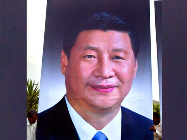 Pakistani-workers-fix-a-billboard-showing-a-picture-of-Chinese-President-Xi-Jinping-to-welcome-him-to-Islamabad-Pakistan-AP-Photo