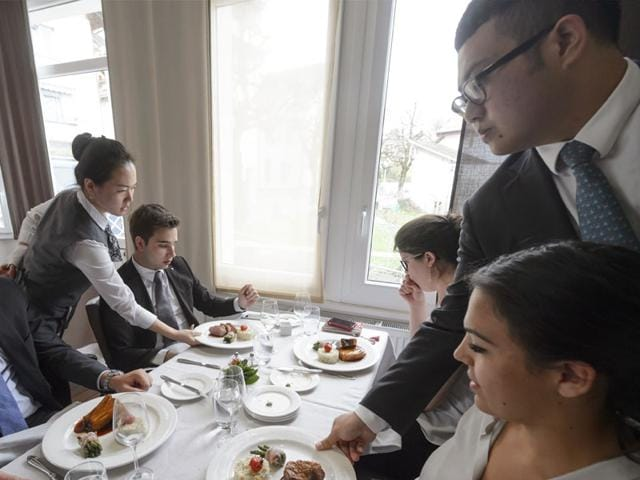 Students-work-during-noon-rush-hour-at-the-Glion-school-one-of-Switzerland-s-famous-hotel-management-schools-in-Glion--It-feels-like-a-five-star-restaurant-with-starched-waiters-pouring-pricy-wine-and-explaining-the-intricate-details-of-a-gourmet-menu-as-diners-gaze-out-at-a-spectacular-mountain-view-But-all-the-servers-the-impeccably-dressed-guests-and-even-the-kitchen-staff-sending-out-elaborately-decorated-plates-are-in-fact-students-at-one-of-Switzerland-s-famous-hotel-management-schools--AFP-photo