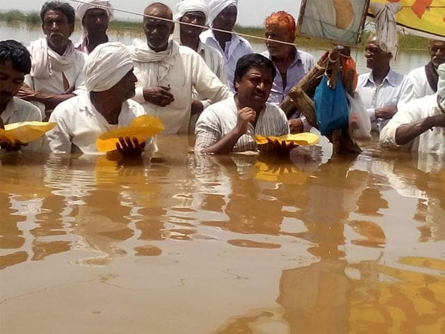Farmers-sitting-on-the-Jal-Satyagraha-partake-of-their-meals-submerged-in-water-at-the-Omkareshwar-dam-Gogalgaon-on-Monday-HT-photo