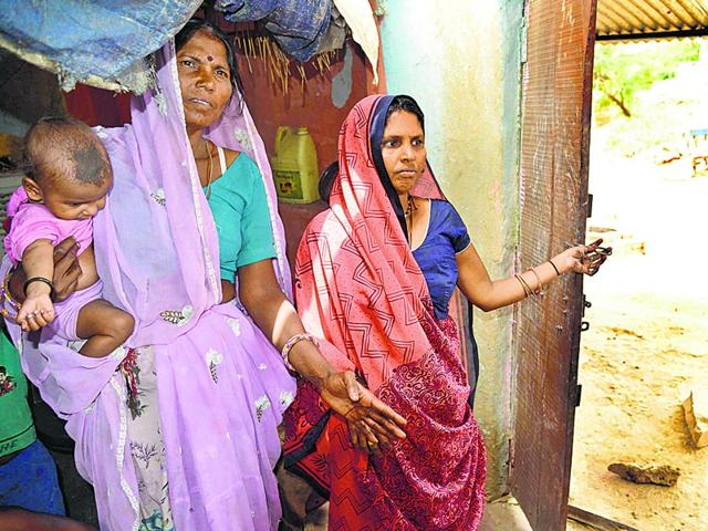 Mamta-Bai-right-and-Moni-Bai-show-broken-door-handle-of-their-house-allegedly-damaged-by-the-accused-AH-Zaidi-HT-Photo