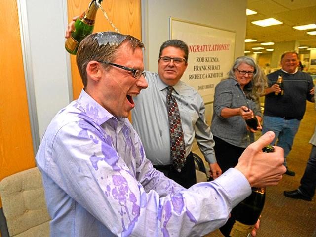 Daily-Breeze-executive-editor-Michael-Anastasi-center-pours-champagne-on-the-head-of-Rob-Kuznia-as-staff-members-celebrate-the-2015-Pulitzer-Prize-for-Local-Reporting-in-Torrance-California-AP-Photo