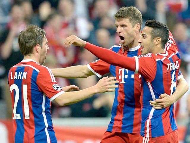 Bayern-Munich-s-midfielder-Thomas-Mueller-celebrates-scoring-with-his-team-mates-defender-Philipp-Lahm-and-Spanish-midfielder-Thiago-Alcantara-during-their-UEFA-Champions-League-second-leg-quarter-final-football-match-against-FC-Porto-in-Munich-AFP-PHOTO