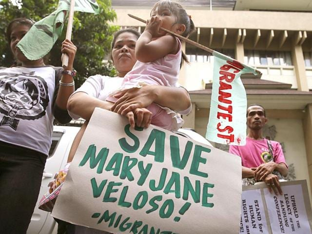 A-mother-carries-her-child-as-they-join-a-rally-outside-the-Indonesian-Embassy-in-the-financial-district-of-Makati-city-east-of-Manila-Philippines-to-appeal-to-the-Indonesian-government-to-spare-the-life-of-convicted-Filipino-drug-trafficker-Mary-Jane-Veloso-AP-Photo