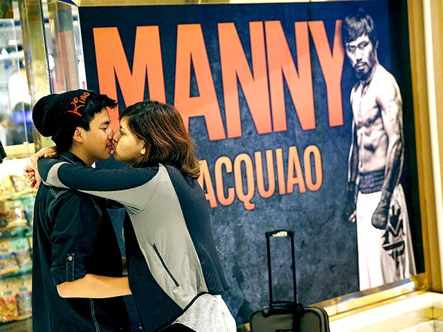 Alex-Moreno-L-and-Giselle-Llamas-kiss-in-the-lobby-of-the-MGM-Grand-in-Las-Vegas-on-Friday-Behind-them-are-advertisements-for-the-fight-between-Floyd-Mayweather-and-Manny-Pacquiao-which-is-scheduled-to-take-place-May-2-at-the-hotel-and-casino-AP-Photo