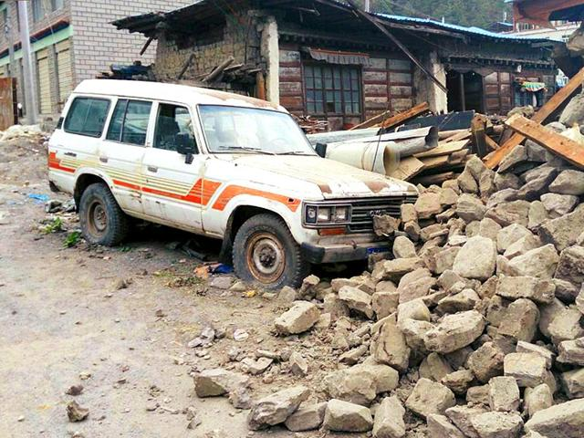 A-car-is-seen-next-to-a-collapsed-house-after-a-7-9-magnitude-earthquake-hit-Nepal-in-Xigaze-Prefecture-Tibet-Autonomous-Region-China-April-25-2015-Reuters-Photo