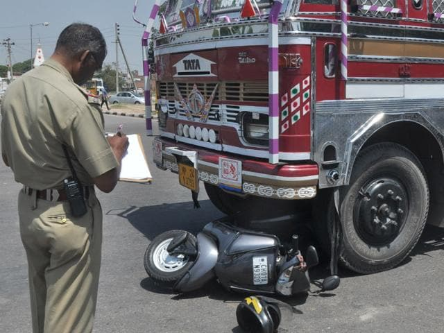 Police-taking-stock-of-the-accident-at-Housing-Board-Chowk-in-Panchkula-in-which-a-scooter-was-seriously-injured-after-being-hit-by-a-truck-on-Saturday-morning-Sant-Arora-HT-Photo