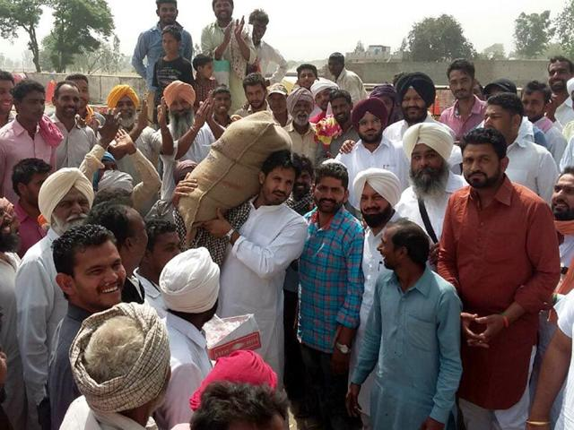 IYC-president-MLA-Amarinder-Singh-Raja-Warring-lifting-wheat-bag-to-protest-the-slow-lifting-of-wheat-in-the-grain-market-of-the-Muktsar-HT-Photo