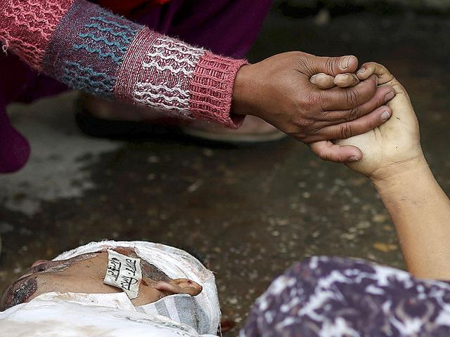 A-woman-holds-the-hand-of-a-deceased-relative-who-died-during-an-earthquake-outside-a-hospital-in-Kathmandu-Reuters
