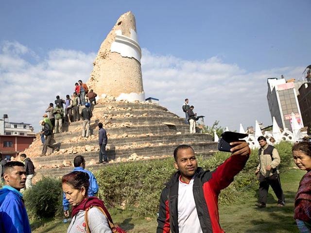 A-man-takes-a-selfie-at-the-Dharahara-Tower-a-city-landmark-that-was-damaged-in-an-earthquake-in-Kathmandu-Nepal-AP-Photo