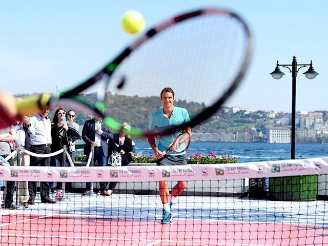 Roger-Federer-returns-the-ball-to-a-young-Turkish-tennis-player-during-an-exhibition-tennis-match-after-a-press-conference-at-the-ATP-Istanbul-Open-in-Istanbul-on-April-27-2015-AFP-Photo