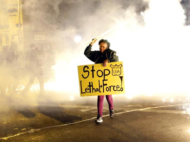 A-woman-runs-for-safety-as-police-throw-tear-gas-canisters-while-enforcing-curfew-AP-Photo