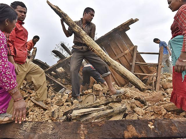 A-man-clears-the-debris-of-his-damaged-house-with-the-help-of-his-family-members-in-Sindhupalchok-district-in-Nepal-Gurinder-Osan-HT-Photo