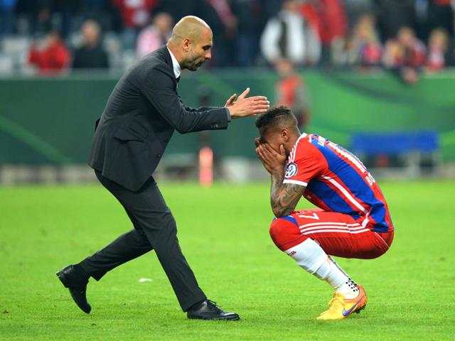 Bayern-Munich-coach-Pep-Guardiola-L-comforts-defender-Jerome-Boateng-after-the-German-Cup-DFB-Pokal-semi-final-against-Borussia-Dortmund-in-Munich-southern-Germany-on-April-28-2015-Dortmund-won-the-match-on-penalties-AFP-Photo