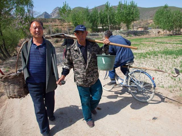 Jia-Wenqi-left-and-Jia-Haixia-right-walk-along-a-lane-in-Yeli-village-near-Shijiazhuang-city-in-northern-China-s-Hebei-province-AP-Photo