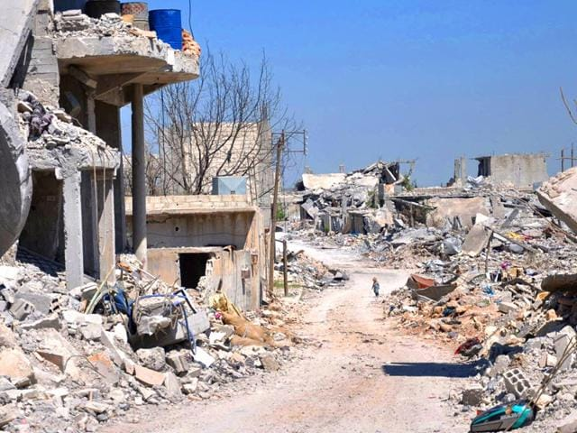 In-this-picture-taken-on-April-18-2015-a-Kurdish-boy-centre-background-walks-between-buildings-that-were-destroyed-during-the-battle-between-the-US-backed-Kurdish-forces-and-the-Islamic-State-fighters-in-Kobani-north-Syria-AP-Photo