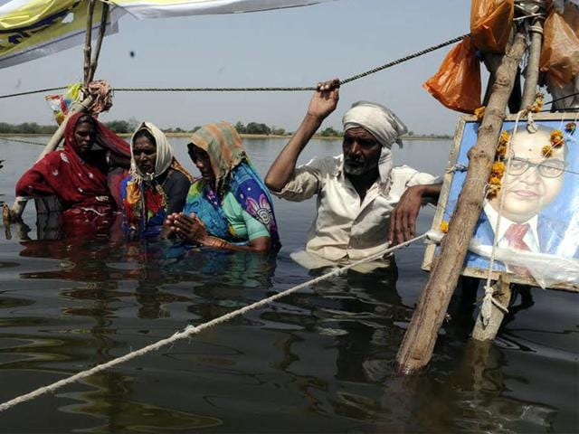 Senior-residents-of-Ghogalgaon-village-move-closer-to-join-30-villagers-protesting-at-Omkareshwar-dam-backwaters-in-Ghogalgaon-on-Thursday-Shankar-Mourya-HT-photo