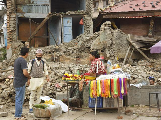 A-woman-sells-temple-paraphenalia-outside-a-damaged-building-near-Pashupatinath-temple-in-Kathmandu-Gurinder-Osan-HT-Photo