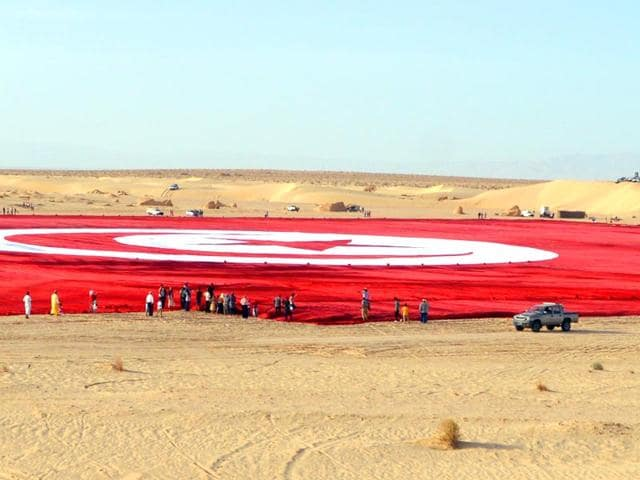 A-picture-taken-on-May-2-2015-shows-a-giant-Tunisian-national-flag-unfurled-at-Ong-Jmel-in-the-southern-desert-AFP-Photo